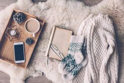 Mug with coffee, smart phone and home decor on wooden serving tray on sheep skin rug. Warm sweater, woolen socks and open book, winter weekend concept, top view
