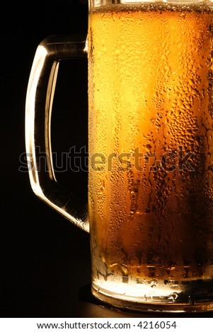Mug with cold beer on a black background