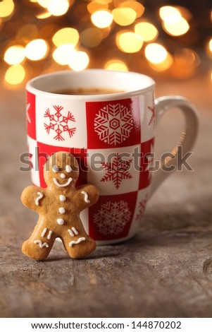 Mug with hot drink and gingerbread cookie.
