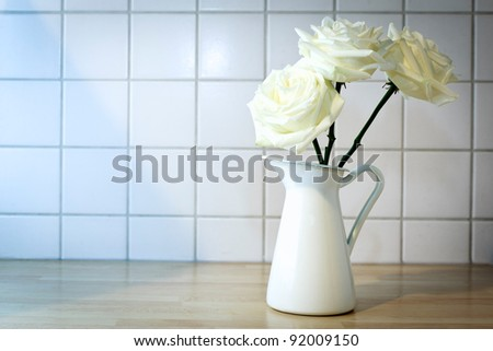 Mug with roses on a countertop in front of white tiles.