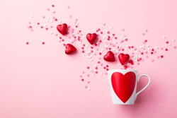 Mug with sugar and chocolate hearts on pink background. Flat lay composition. Romantic, St Valentines Day concept.