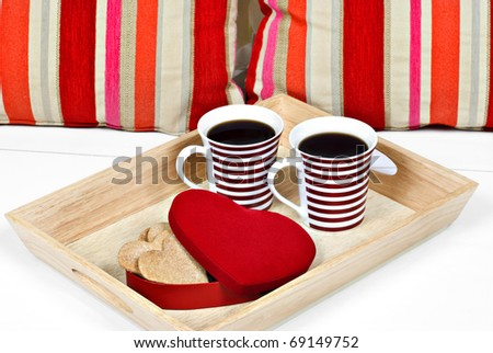 Mugs of coffee with heart shape biscuits in a red heart shaped container