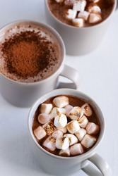 Mugs of hot chocolate cocoa drink, comforting cozy delicious milky mocha topped with roasted toasted marshmallows