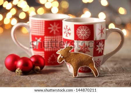Mugs with hot drink and gingerbread cookie.