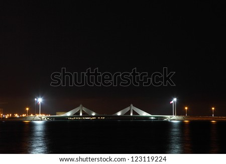MUHARRAQ, BAHRAIN - DECEMBER 17: Beautiful illuminated Sheikh Isa Bin Salman causeway Bridge on 17 December, 2012, Bahrain. The design with two sail-like structures depict  traditional pearl diving
