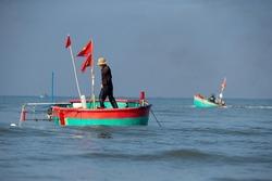 Mui Ne, Vietnam, man in traditional Vietnamese round boat