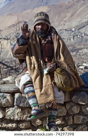 MUKTINATH - DECEMBER 24: Sadhu pilgrim (holy man) seeks alms in front of a Vishnu temple on December 24, 2009 in Muktinath, Lower Mustang District, Central Nepal