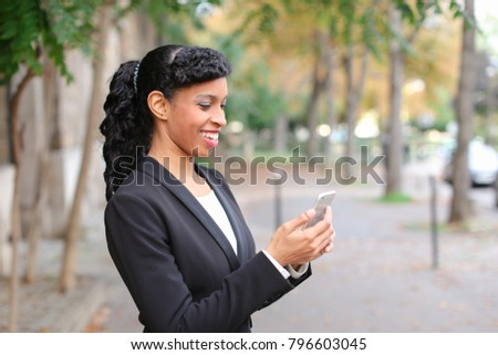 Mulatto fiancee talking with truelove on smartphone in park with close up of beautiful face. Young girl has brown eyes, dark hair and heartfelt smile. Concept of new technologies and advantageous