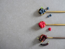 mulberry, blueberries and raspberries, served on spoons on a gray background