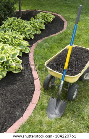 Mulch bed around the house and wheelbarrow along with a shovel.