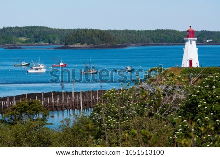 Mulholland Point lighthouse tower overlooks harbor with fishing boats nearby in summer. The wooden beacon lies on Campobello Island in Canada. #1051513100