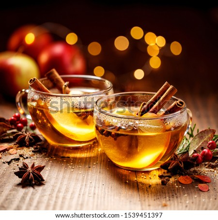 Mulled cider with apple slices, cinnamon, cloves, anise stars and citrus fruits in glass cups on a wooden rustic table. Delicious christmas hot drinks on a wooden rustic table.