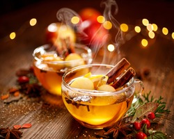 Mulled cider with slice apples, cinnamon, cloves, anise stars and citrus fruits in glass cups on a wooden rustic table, close-up. Delicious,  traditional hot drink