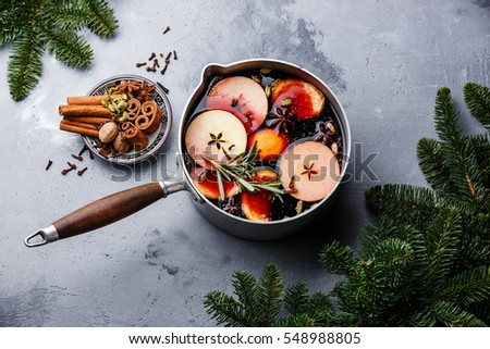 Mulled wine hot drink with citrus, apple and spices in aluminum casserole and Fir branch on concrete background Сток-фото ©