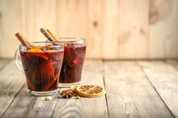 Mulled wine in glass glasses with apples, orange, cinnamon and star anise. Hot christmas drink on rustic background copy space.