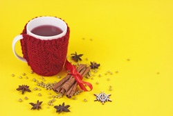 Mulled wine in mug with woolen case on yellow background.cup in beuatiful knitting red case with spices and golden glitters.Holiday xmas backdrop with copy spase.Christmas New Year greeting card.