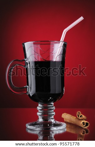 Mulled wine in the glass and cinnamon on red background