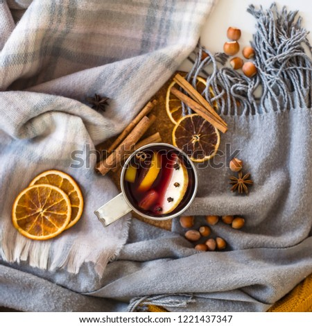Mulled wine with apple, orange, clove, cinnamon and anise in a metal mug among winter plaids, scarves and sweaters. Hot drink on the eve Christmas eve #1221437347