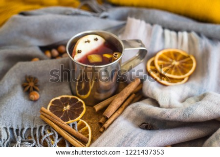 Mulled wine with apple, orange, clove, cinnamon and anise in a metal mug among winter plaids, scarves and sweaters. Hot drink on the eve Christmas eve #1221437353