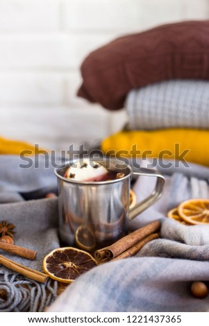 Mulled wine with apple, orange, clove, cinnamon and anise in a metal mug among winter plaids, scarves and sweaters. Hot drink on the eve Christmas eve