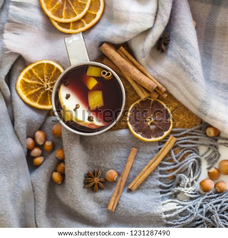 Mulled wine with apple, orange, clove, cinnamon and anise in a metal mug among winter plaids, scarves and sweaters. Hot drink on the eve Christmas eve #1231287490