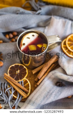 Mulled wine with apple, orange, clove, cinnamon and anise in a metal mug among winter plaids, scarves and sweaters. Hot drink on the eve Christmas eve #1231287493