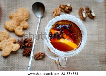 mulled wine with cinnamon and star anise with slice of orange and spices and Christmas cakes, with decorated background
