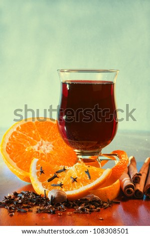 Mulled wine with orange and spices on the table against green background