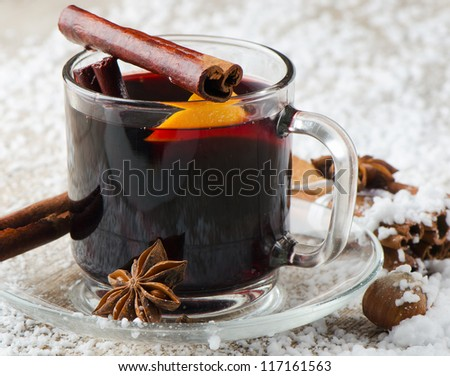 mulled wine with spices  and orange on a wooden table