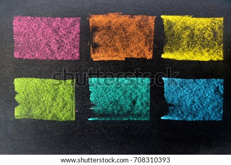Multi color chalk drawing as striped line on black board background