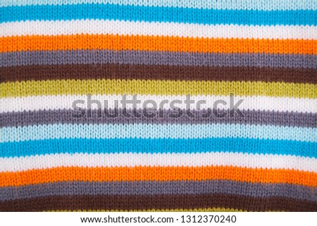 Multi color - orange, white, blue, grey, green. Striped Fabric Knit Cloth Texture. Abstract Close up Line Pattern Background #1312370240