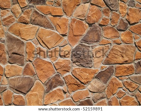 Multi-colored and multi-sized, orange and brown rock wall grunge texture background.