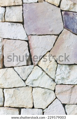 Multi-colored and multi-sized, pale rocks wall grunge texture background.
