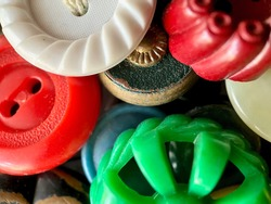Multi-colored antique or vintage sewing buttons: Celluloid Buttons, Bakelite Buttons, Lucite Buttons, vegetable Ivory, metal, China, glass, and mother of pearl.