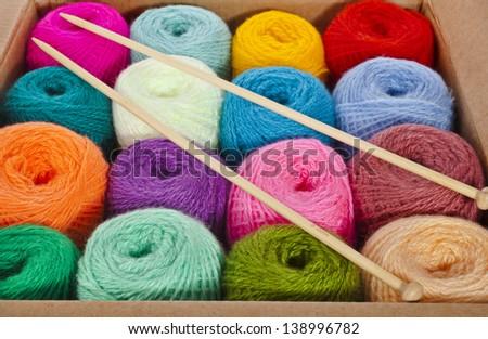 multi-colored balls of wool knitting yarn in a cardboard box