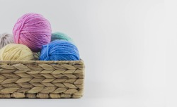 Multi-colored balls of yarn for knitting lie in a wicker basket. Place for text.