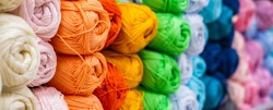 Multi-colored balls of yarn for knitting. Woolen threads for needlework. Banner format