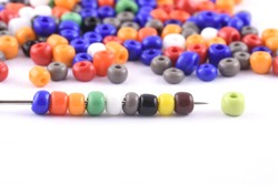 Multi colored Beads spread on white background with needle. Beads with needle . Close up, macro,finishing fashion clothes. make bead necklace, beads for women of fashion,Bead Crochet. Daily Beading.