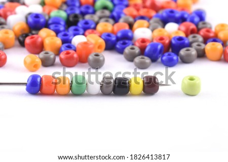 Multi colored Beads spread on white background with needle. Beads with needle . Close up, macro,finishing fashion clothes. make bead necklace, beads for women of fashion,Bead Crochet. Daily Beading. Foto d'archivio ©