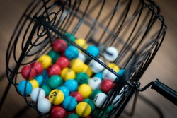 Multi-colored bingo balls in cage sitting on a desk.
