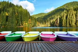 Multi-colored boats at the pier on Lake Lacu Rosu, Romania. Autumn landscape of mountain lake, forest and mountains.