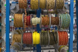 multi-colored bright golden braid wound on bobbins located on the counter of the store for decoration, sewing and needlework