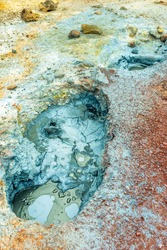 Multi colored bubbling hot pool and colorful soil , rocks and dirt in geothermal and volcanic area in Iceland. Texture and pattern concept.
