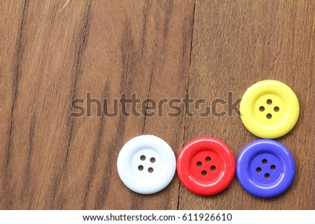 Multi-colored button or stud or buckle placed on the wood. #611926610
