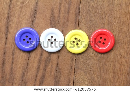 Multi-colored button or stud or buckle placed on the wood. #612039575