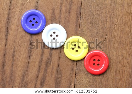 Multi-colored button or stud or buckle placed on the wood. #612501752