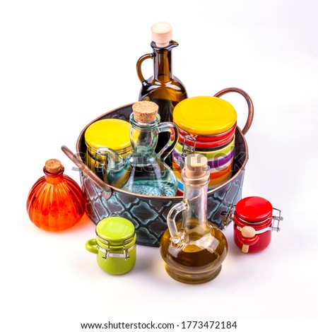 Multi-colored ceramic containers and glass bottles for spices, oil and vinegar in a vintage metal tray