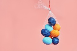 multi-colored chicken eggs in  bag mesh hang on pink background. easter