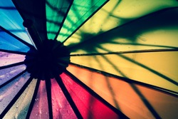 Multi-colored colorful umbrella with all colors of the rainbow with raindrops. Vintage, grunge, old, retro style photo.