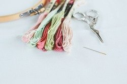 multi-colored cotton floss thread for cross-stitch, a needle, scissors and a wooden hoop on a white canvas